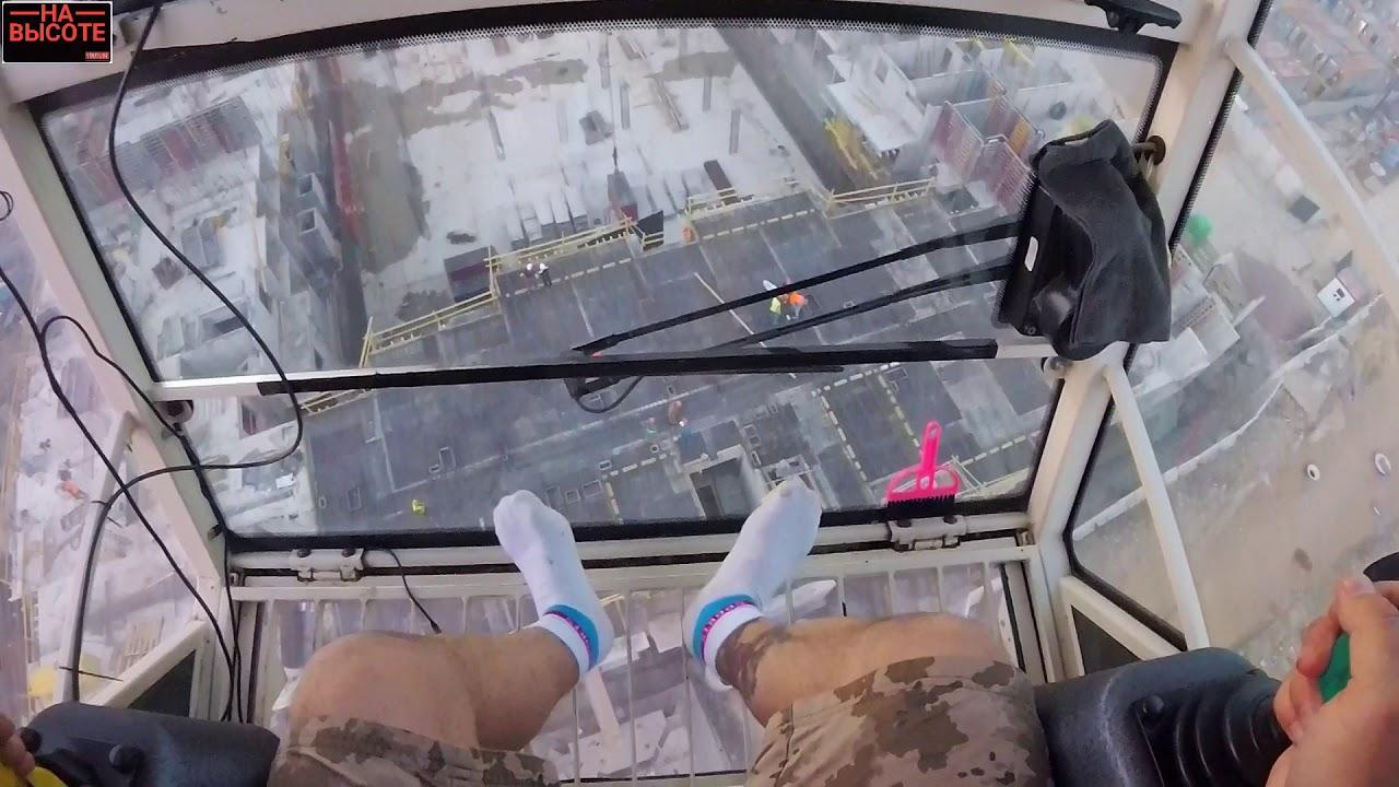 Крановщик во время шторма на башенном кране. Crane operator during a storm on a tower crane.